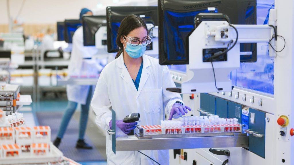 Investigadora de atención médica de Mayo Clinic Laboratories, una mujer blanca que usa anteojos y equipo de protección personal, mascarilla y guantes mientras trabaja en el laboratorio con tubos de ensayo