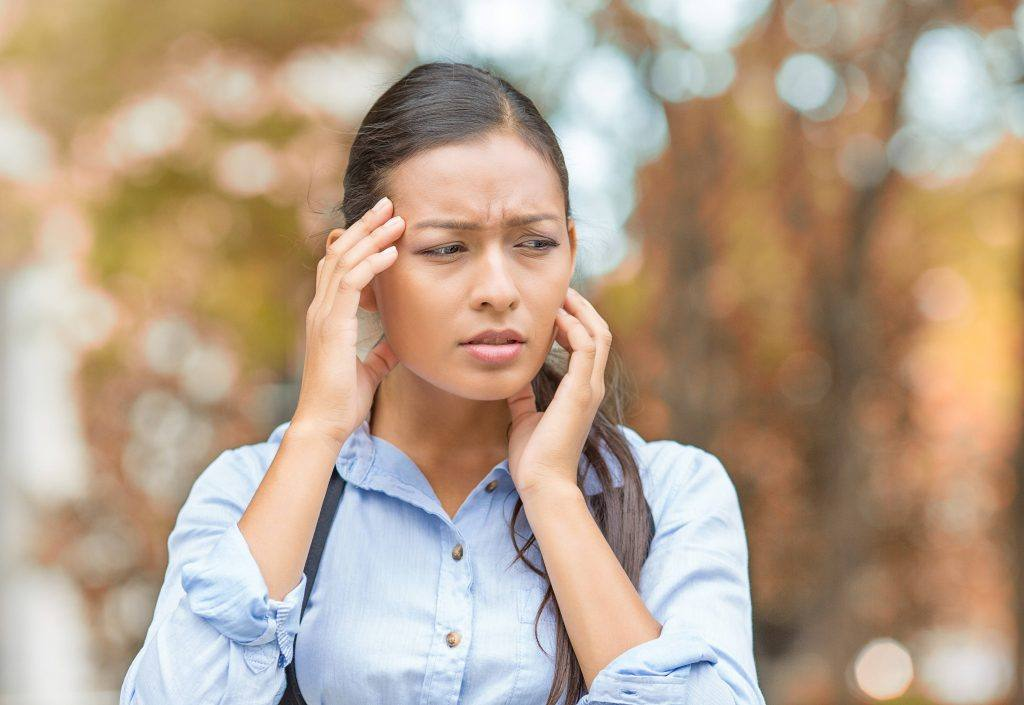 a young woman outside, perhaps Latina, with a stressful, worried look on her face and touching her forehead like she has a headache