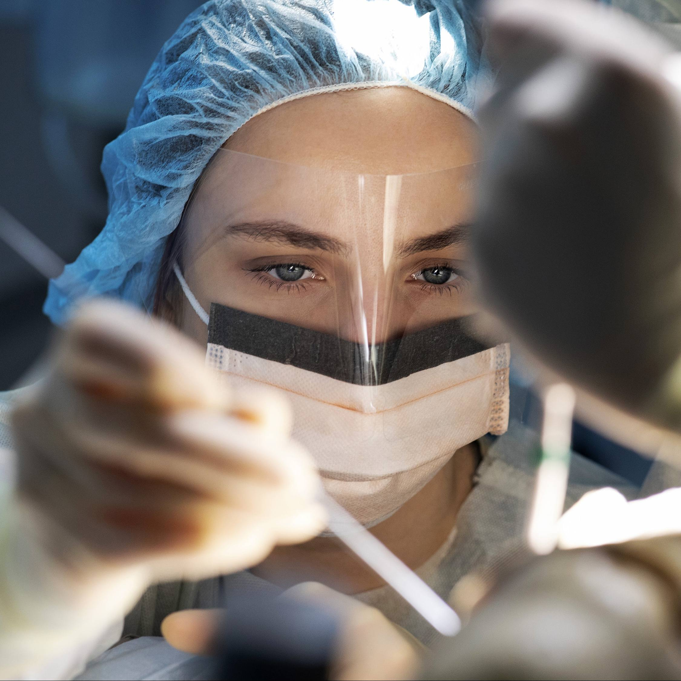 a Mayo Clinic surgeon, a white woman, wearing PPE, including a face shield in the operating room during COVID-19 pandemic
