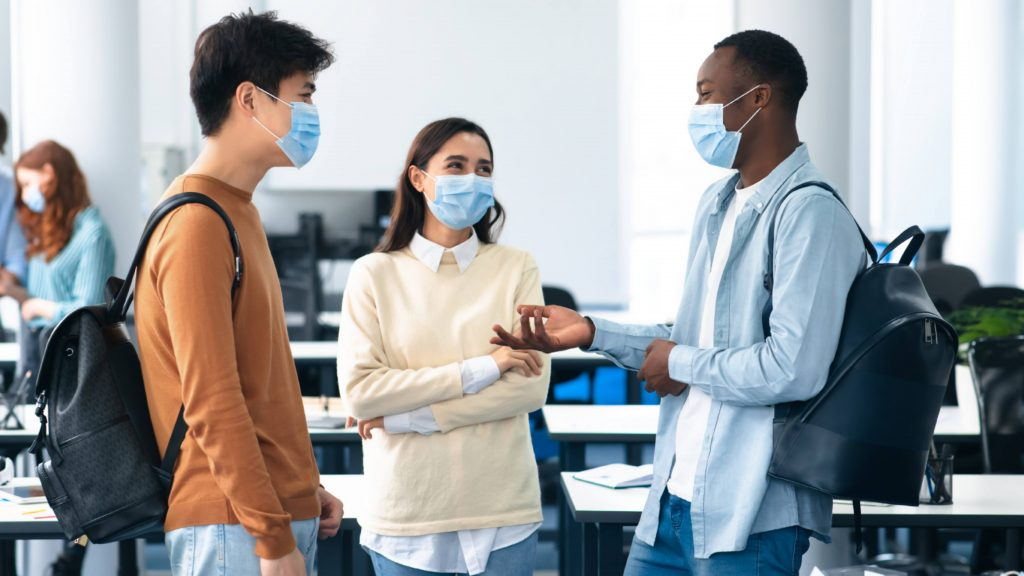 a group of three diverse college students, smiling and talking, wearing face masks and carrying backpacks in a school classroom