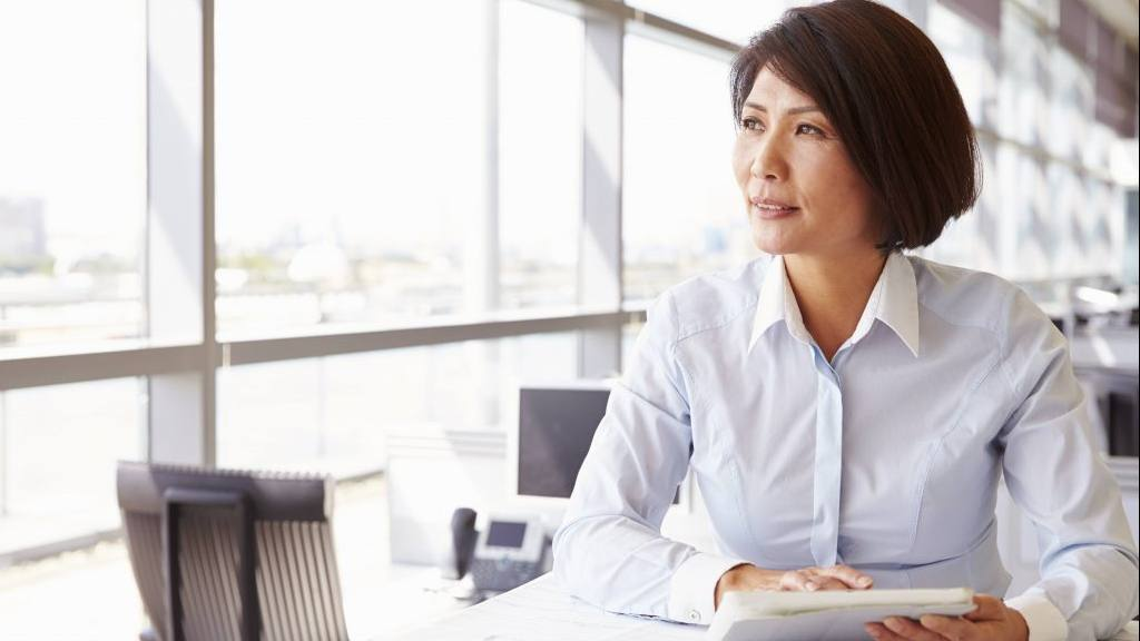 a middle-aged Asian women sitting at an office table, holding an iPad and looking out a window