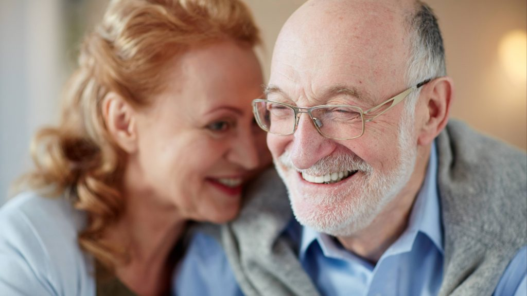 a middle aged white male with slightly gray hair, balding, wearing glasses and smilng with a white middle aged woman, perhaps his wife, who is smiling and putting head near his shoulder