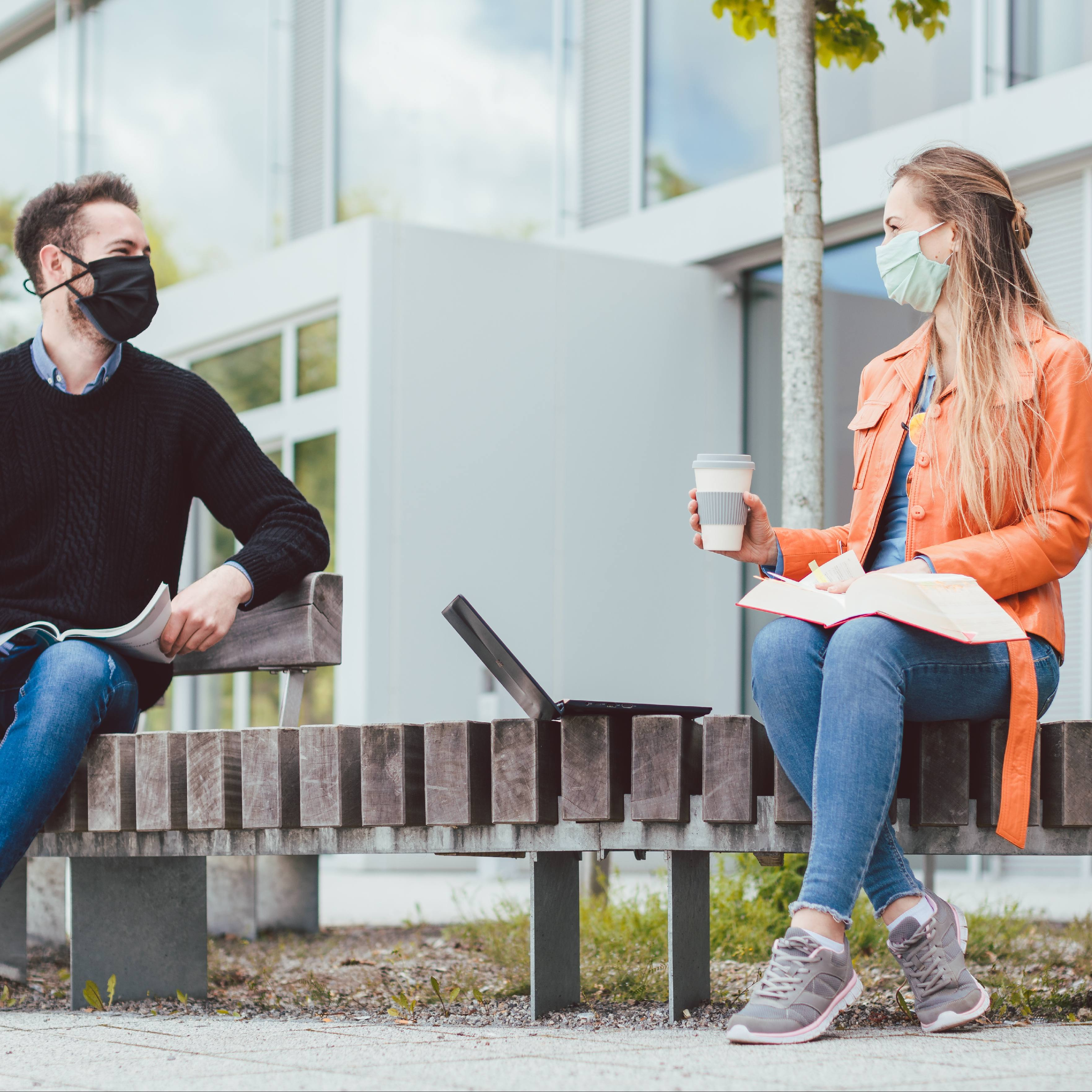 a young white male wearing a mask and sitting on a bench ouside, at least six feet away from a young white female, praticing COVID-19 social distancing
