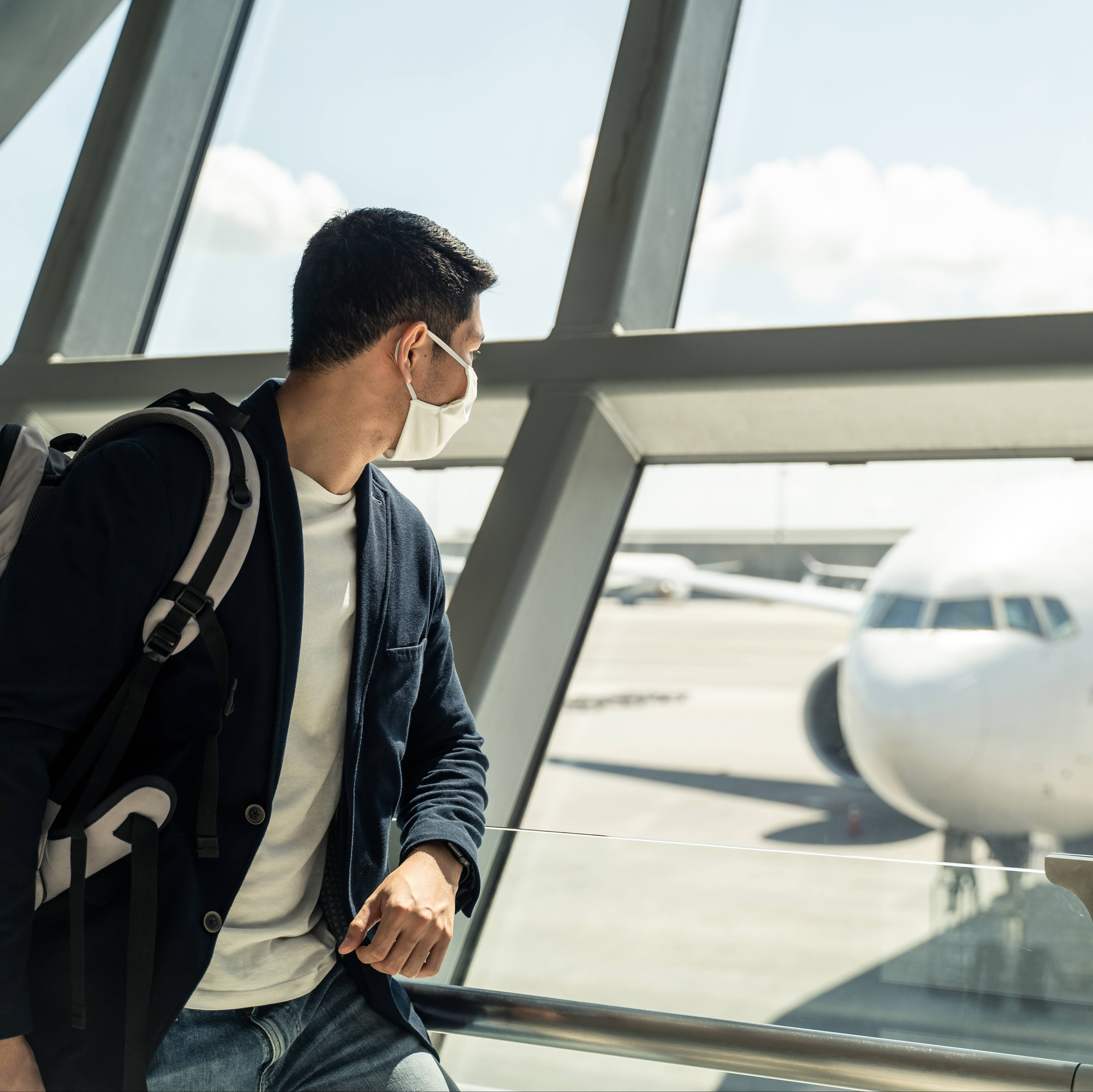 a young white, perhaps college aged man, wearing a back pack and a face mask, in an airport looking like he's ready to travel and watching an airplane out a window.