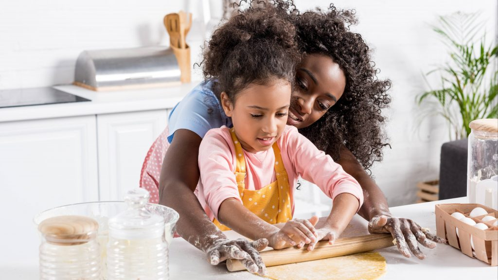an adult Black woman, perhaps a mother, helping a little Black girl, perhaps her daughter, with baking in the kitchen and rolling out a pie crust