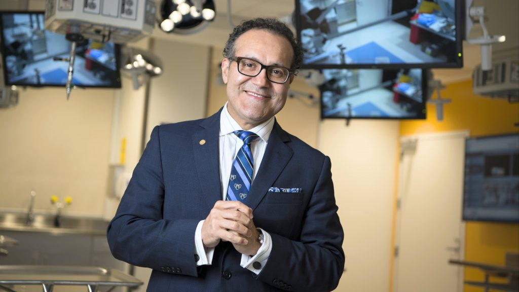 neurosurgeon Dr. Alfredo Quinones-Hinojosa, Dr. Q wearing a suit and standing in a operating room with monitors behind him