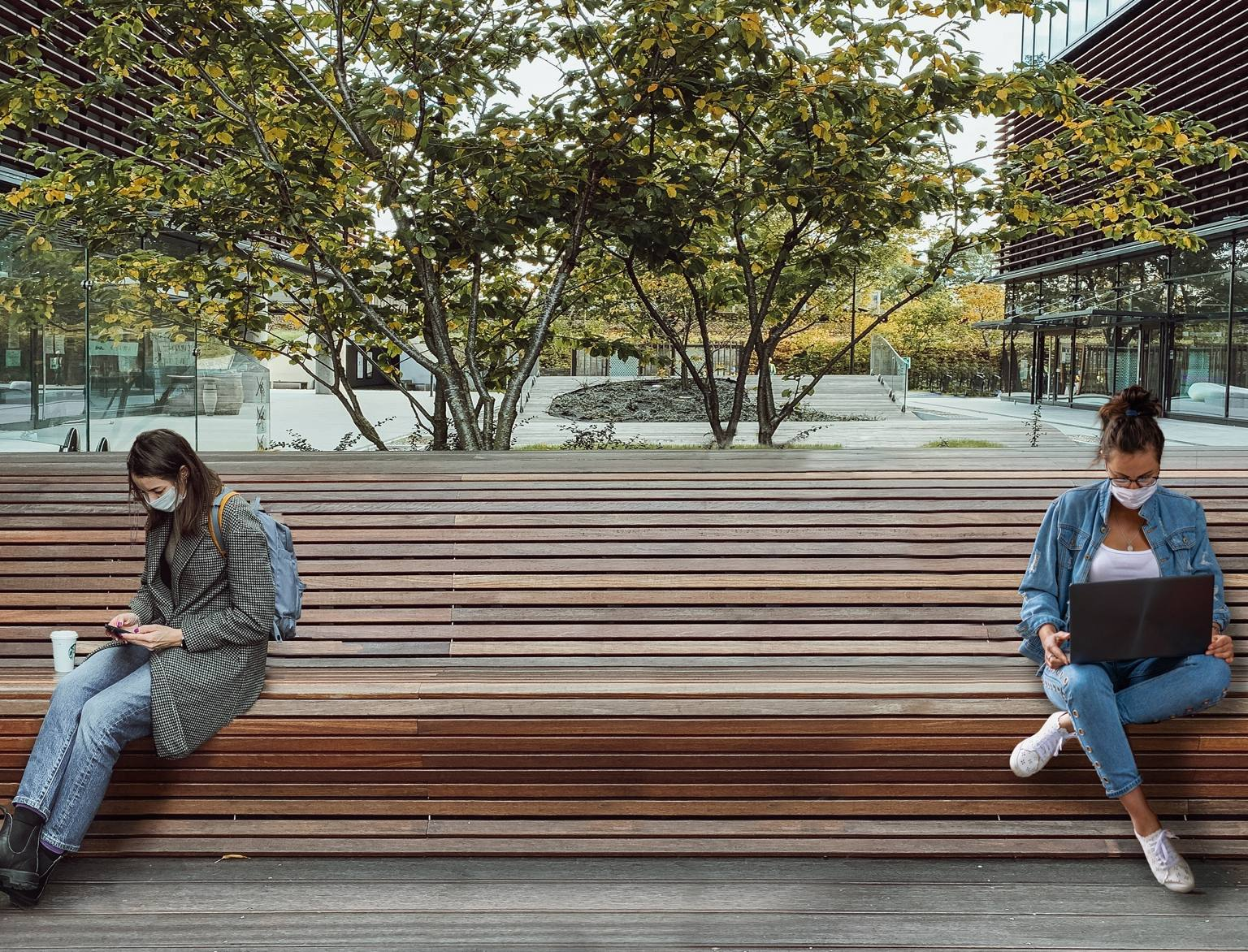 two masked people, sitting 6 feet apart on a bench