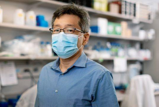 Wearing a facemask in the laboratory, Hideki Ebihara, Ph.D., a Mayo Clinic virologist who leads Mayo's Emerging Virus Program.