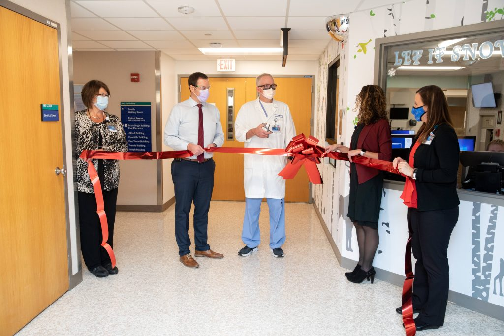 four NICU staff cutting red ribbon for opening of new space