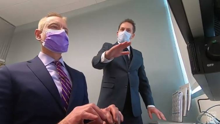 Dr. Laskowki wearing a facemask and sitting at a computer with a colleague, also wearing a facemask, demonstrating ergonomic recommendations