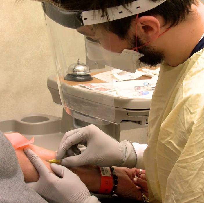 Mayo Clinic nurse, a white man, wearing PPE including a face shield while adminstering monoclonal antibody treatment during COVID-19