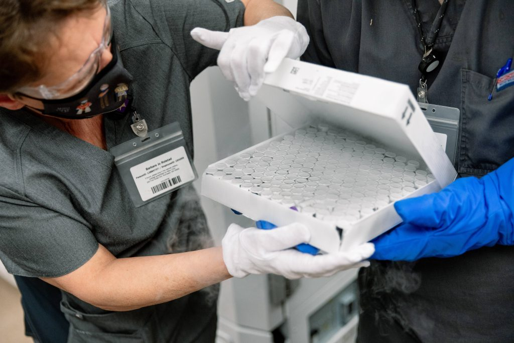 Mayo Clinic medical staff in Rochester, wearing PPE, inspecting a box of Pfizer vaccine vials after arrival
