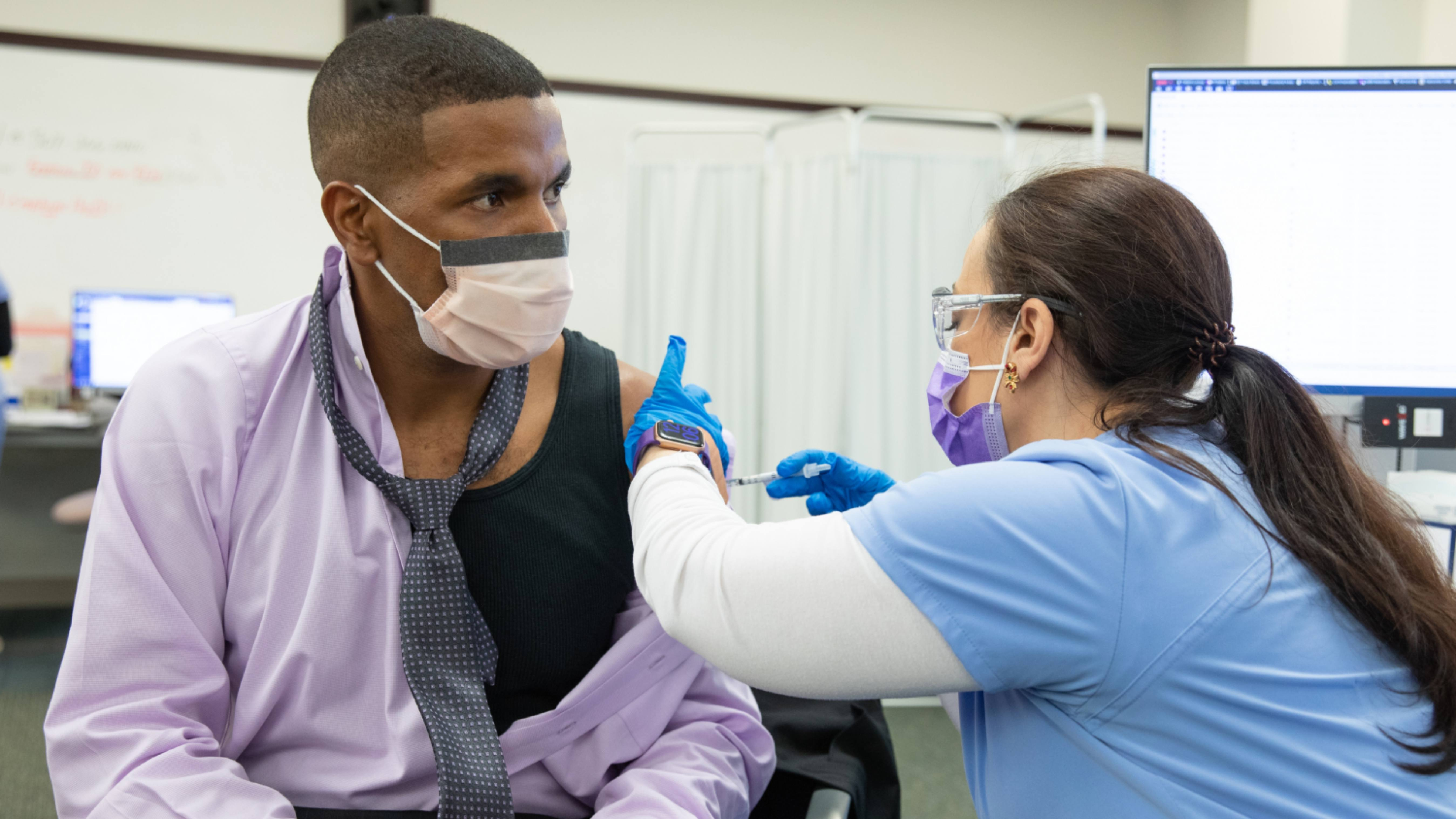 a Mayo Clinic employee in Florida, a Black man, wearing a mask and receiving the COVID-19 vaccine