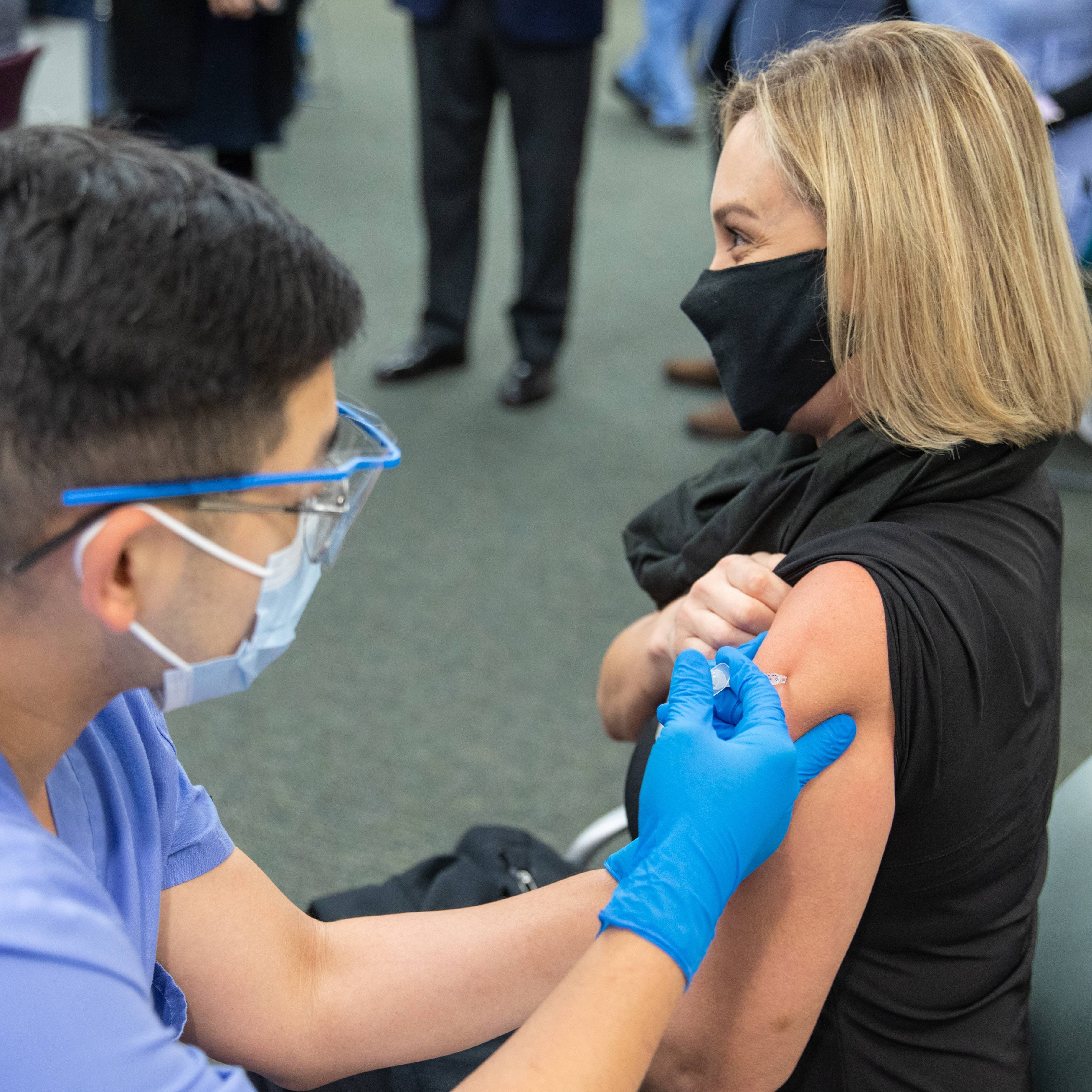 a Mayo Clinic in Florida employee, a white woman, getting her COVID-19 vaccine administered by a Mayo nurse , a man perhaps of Asian ethnicity wearing PPE