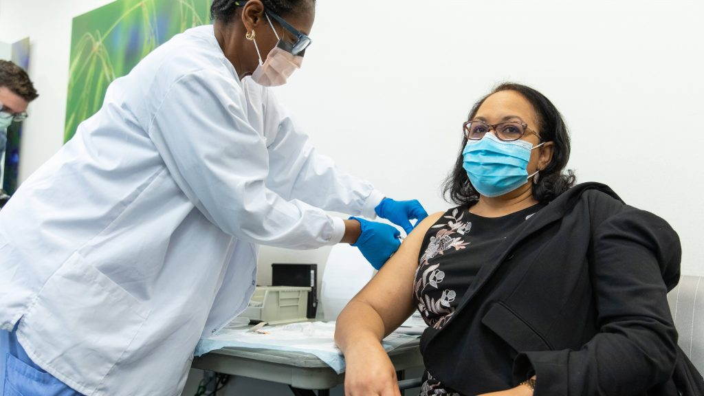 a Mayo Clinic in Florida nurse, a Black woman in PPE administering a COVID-19 vaccine to a Mayo employee, perhaps a Latina woman in a black jacket getting her vaccination