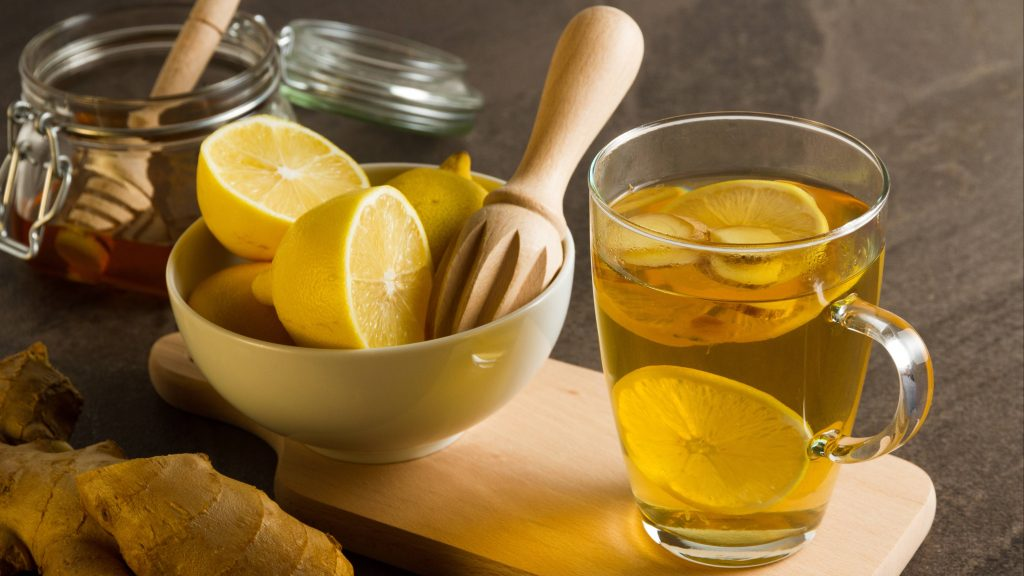 a kitchen counter with a bowl of lemons on a cutting board, a jar of honey, fresh ginger root and a clear glass of body cleansing juice