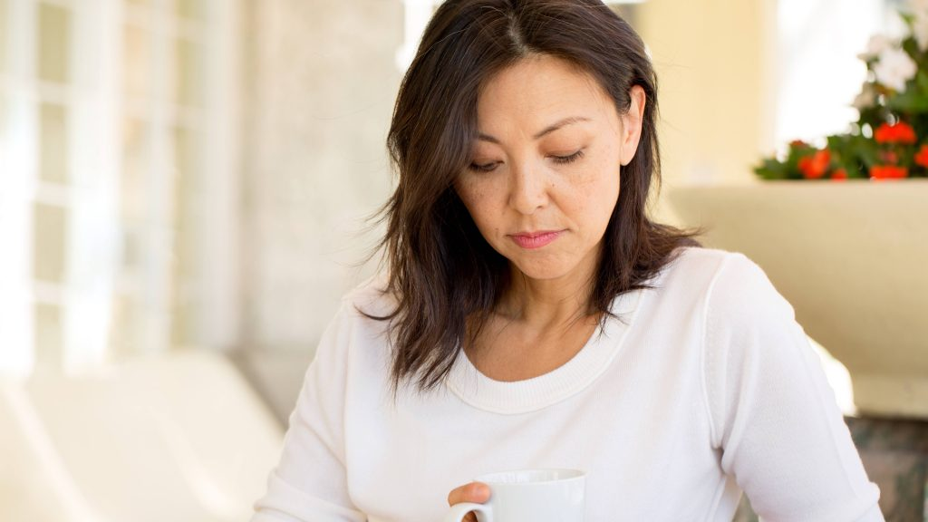a middle aged woman, with light brown skin tone, perhaps Latina or Asian, holding a coffee mug and looking sad, worried, depressed