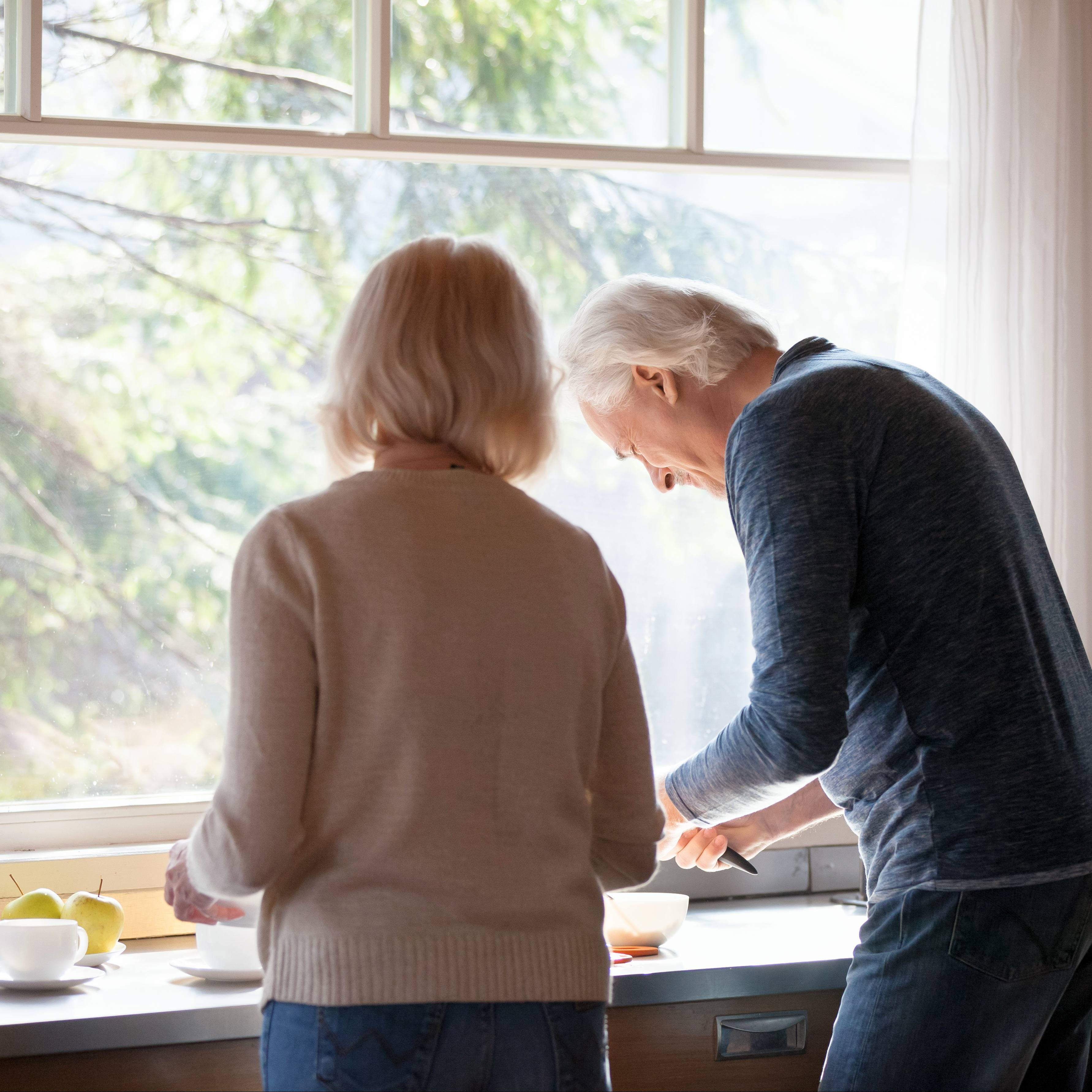 a white adult woman and man, middle-aged, working together at a kitchen counter near a sink and a sunny window, cutting fruit