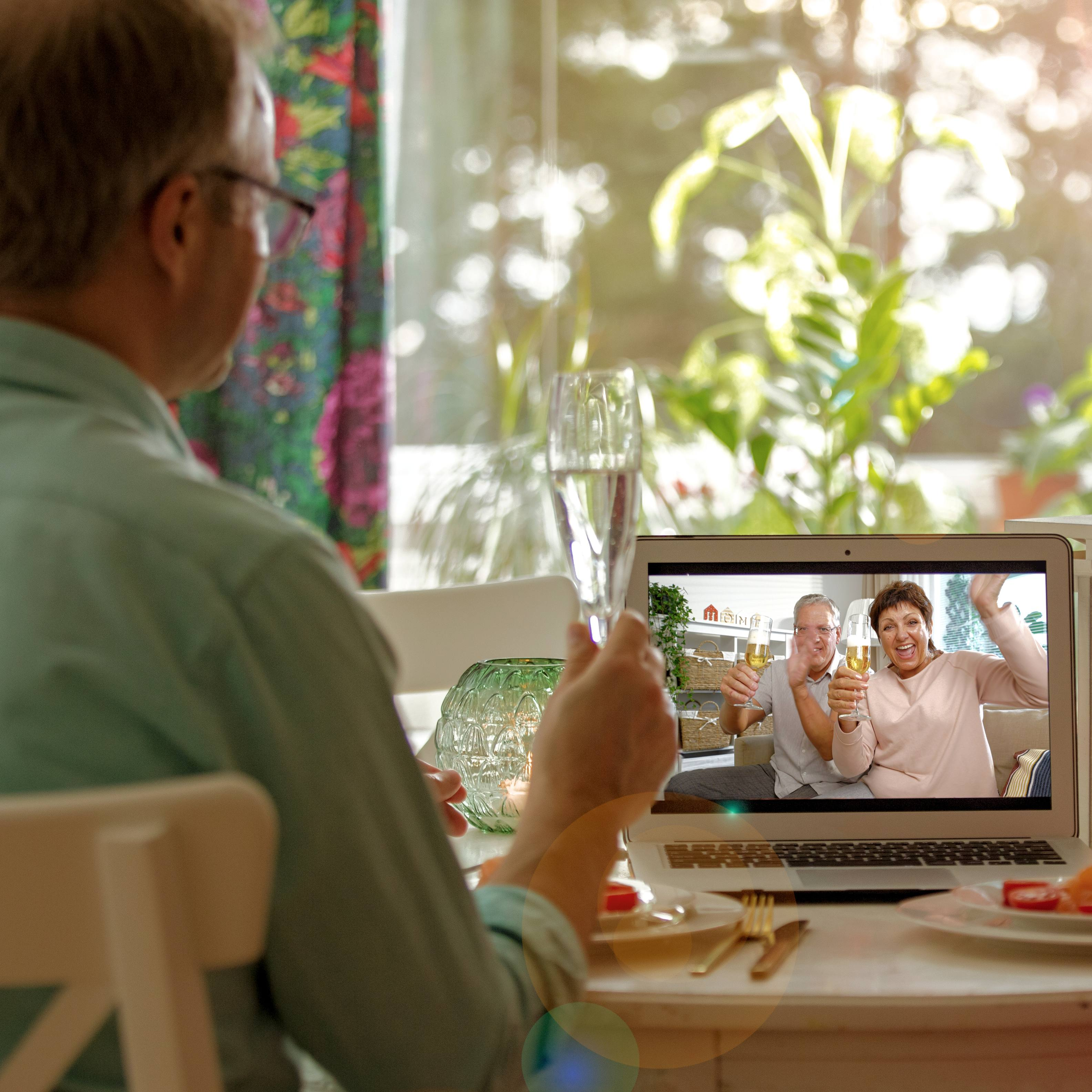 a white man and a white woman sitting at a dinner table with glasses of champagne greeting friends or family members over a virtual meeting on a laptop