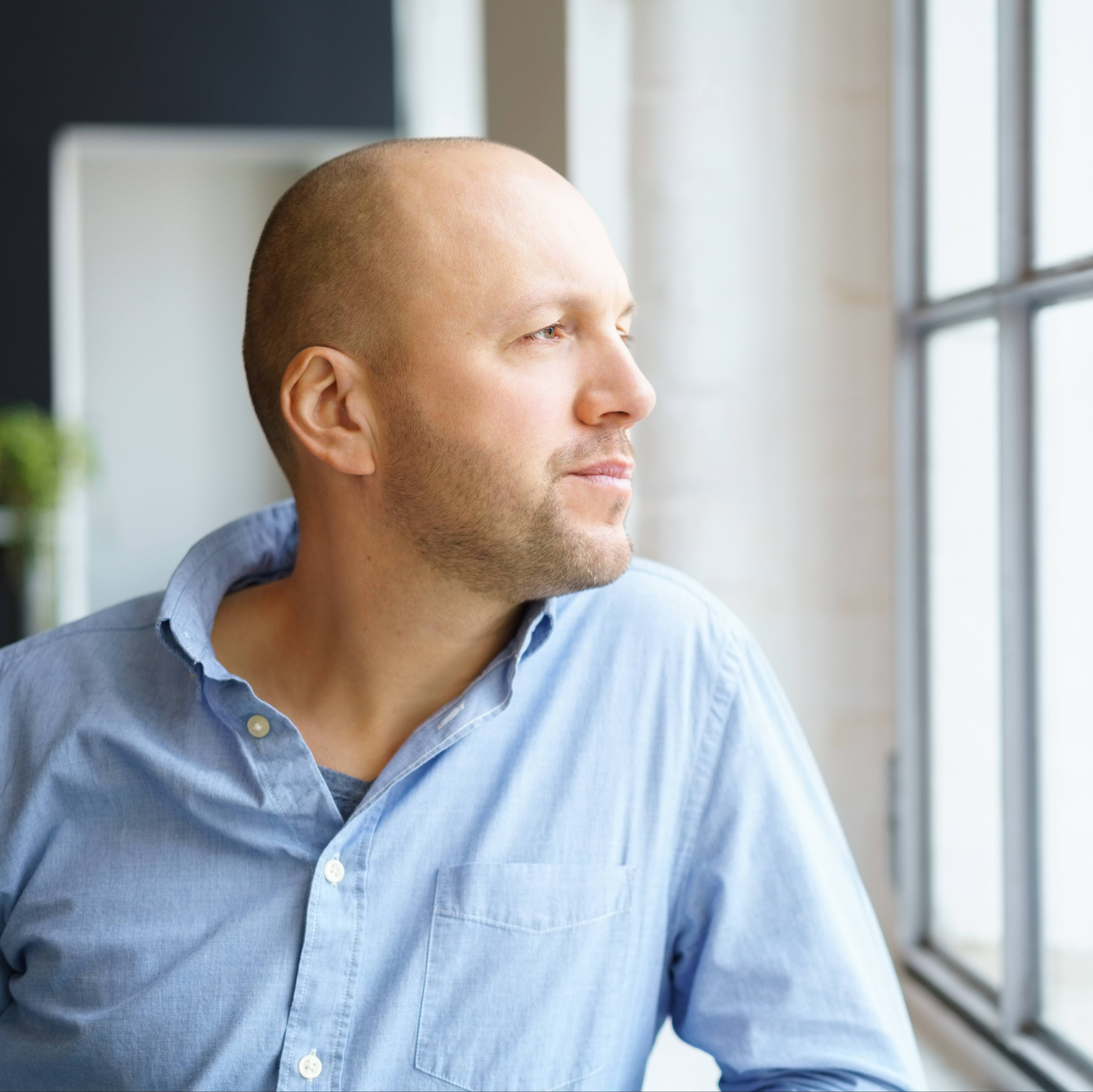 a white man in a blue shirt, looking serious, worried and thoughtful while standing at a window looking out
