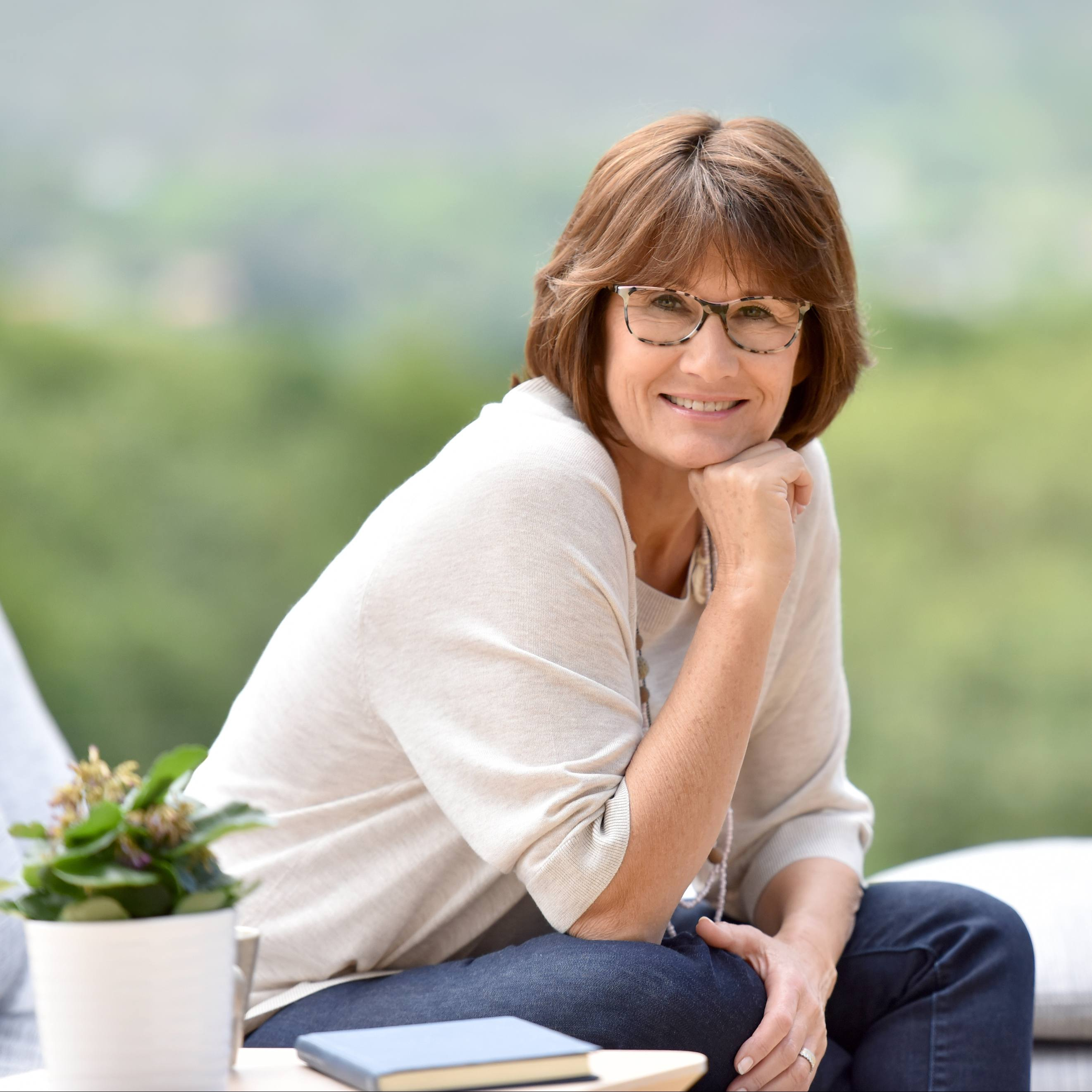 a white woman with short brown hair and glasses, sitting on an outside couch and smiling
