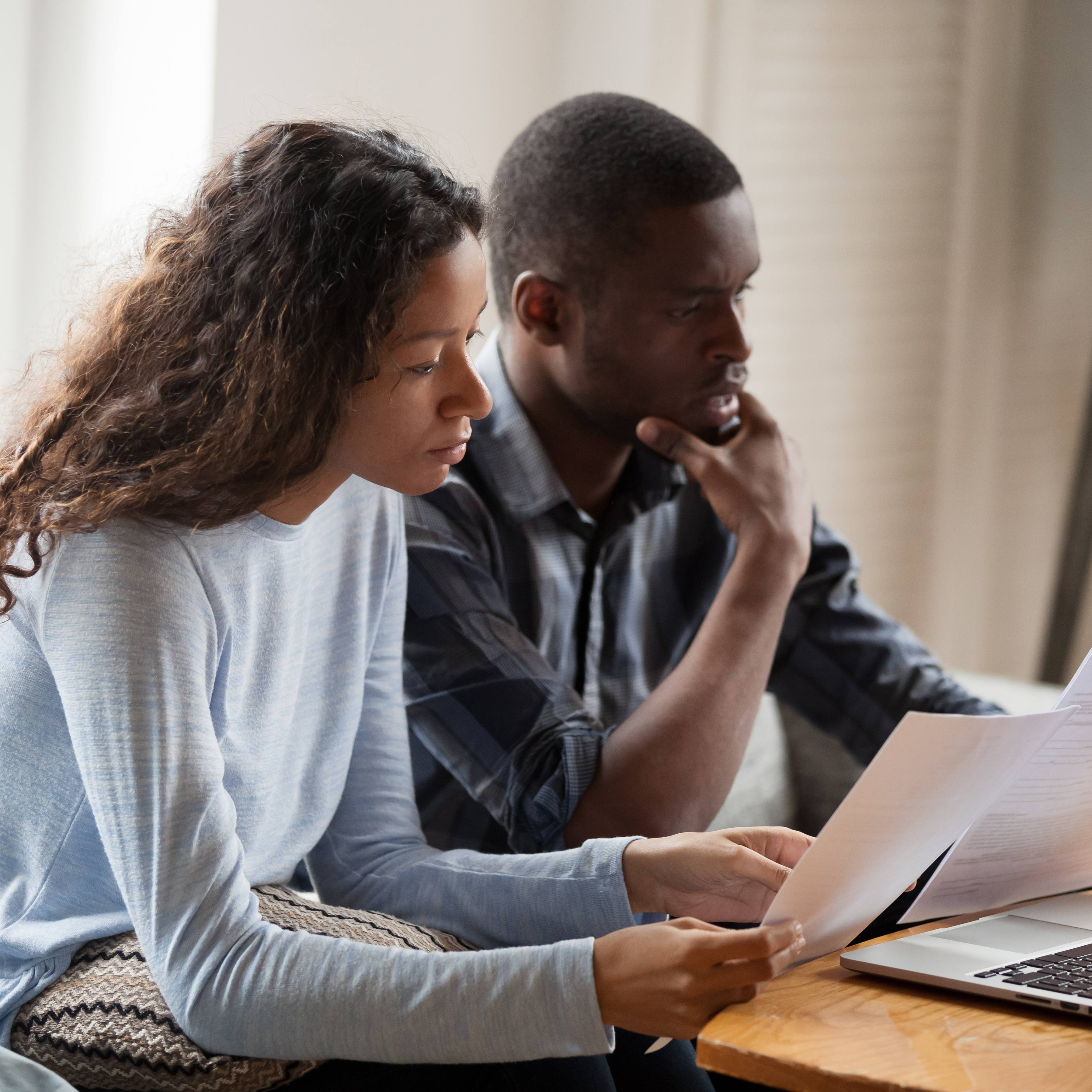 a young Black woman and young Black man sitting together on a couch looking seriously at information on a computer and reading paper documents