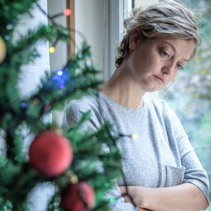 a young white woman looking sad and depressed, leaning against a glass door, with a decorated Christmas tree in the foreground