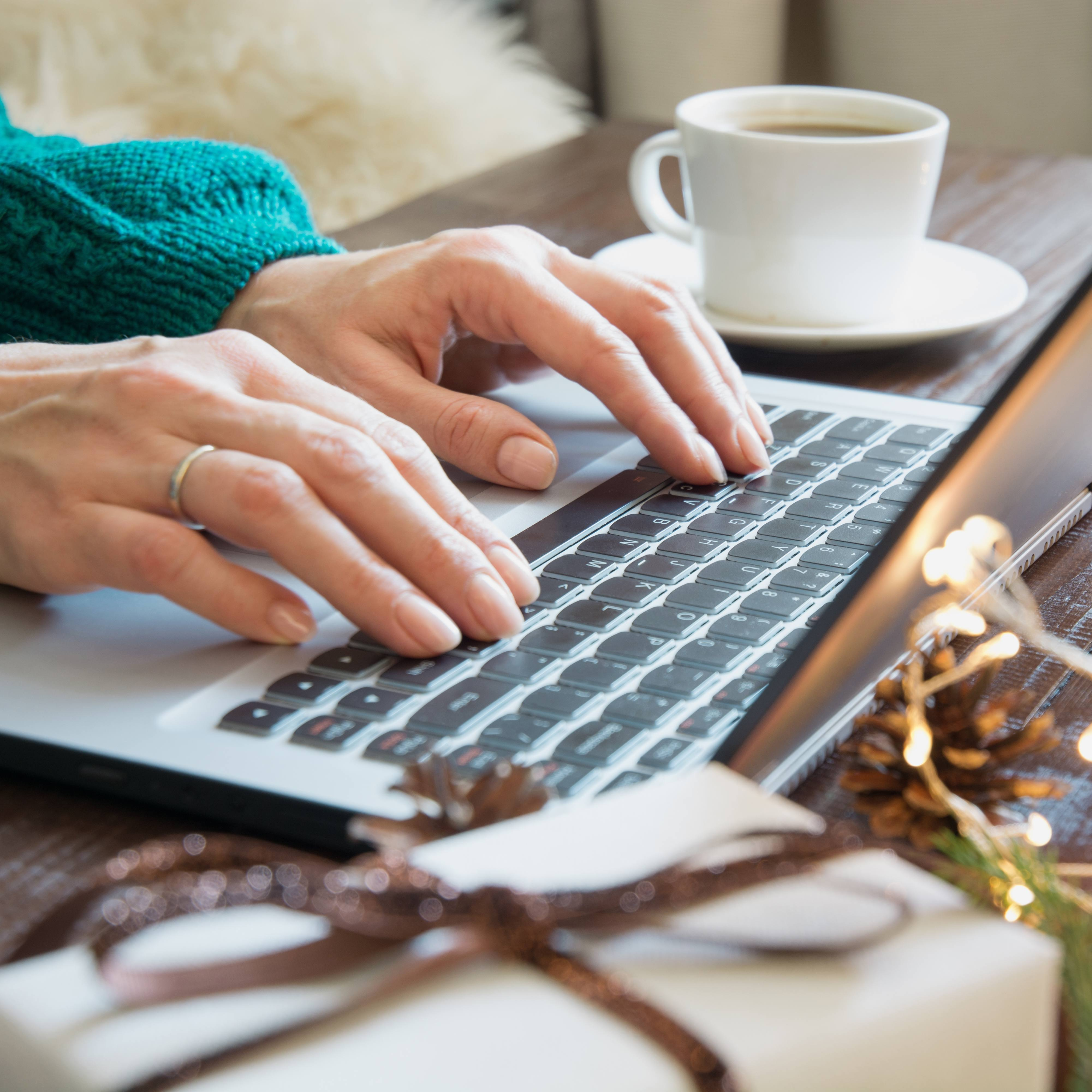 closeup of a white woman's hands typing on a computer laptop with a cup of coffee nearby and a small Christmas tree with tinsel on the table