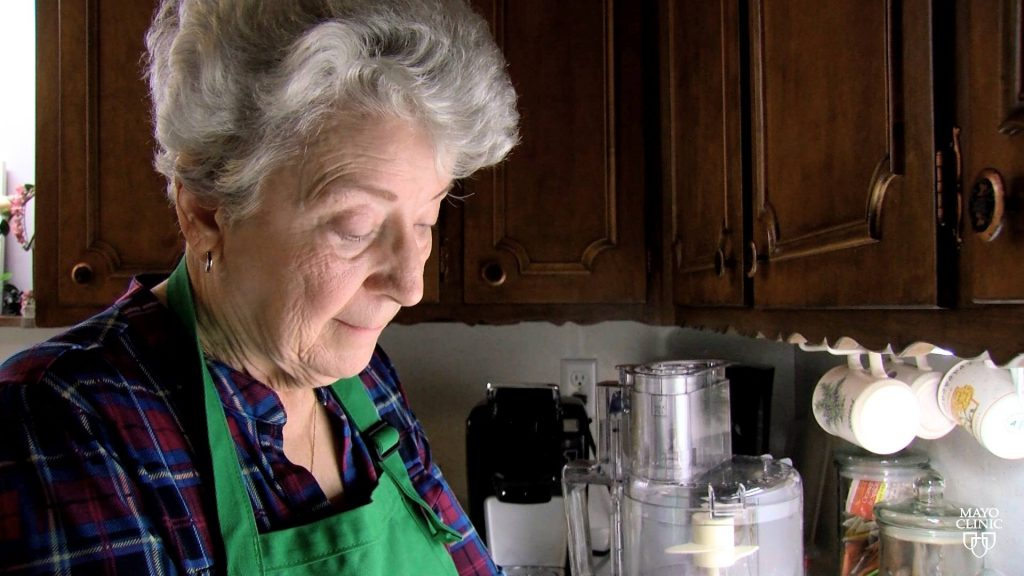 liver cancer patient Sharon in her kitchen, wearing an apron, and mixing something on the counter.