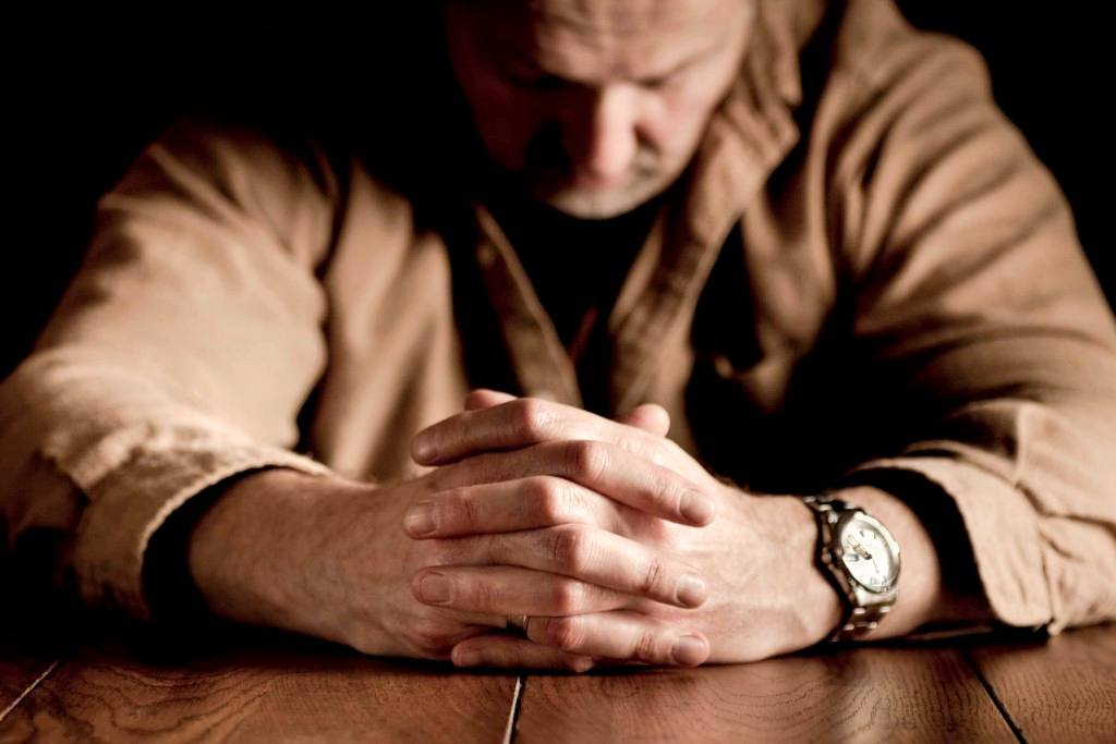 a white man with his hands clasped as if praying, sitting at table sad, thoughtful, depressed