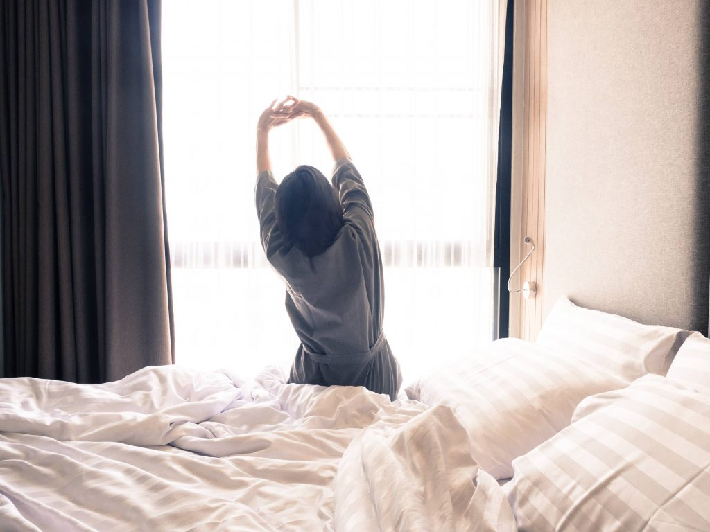 a white woman sitting on the edge of a bed in a robe, looking out a window and stretching her arms up in the air for morning exercise