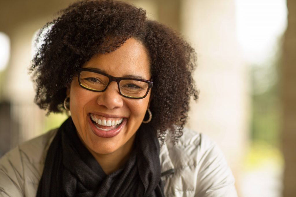 a middle aged Black woman with short hair, glasses and earrings on, laughing and smiling, looking happy