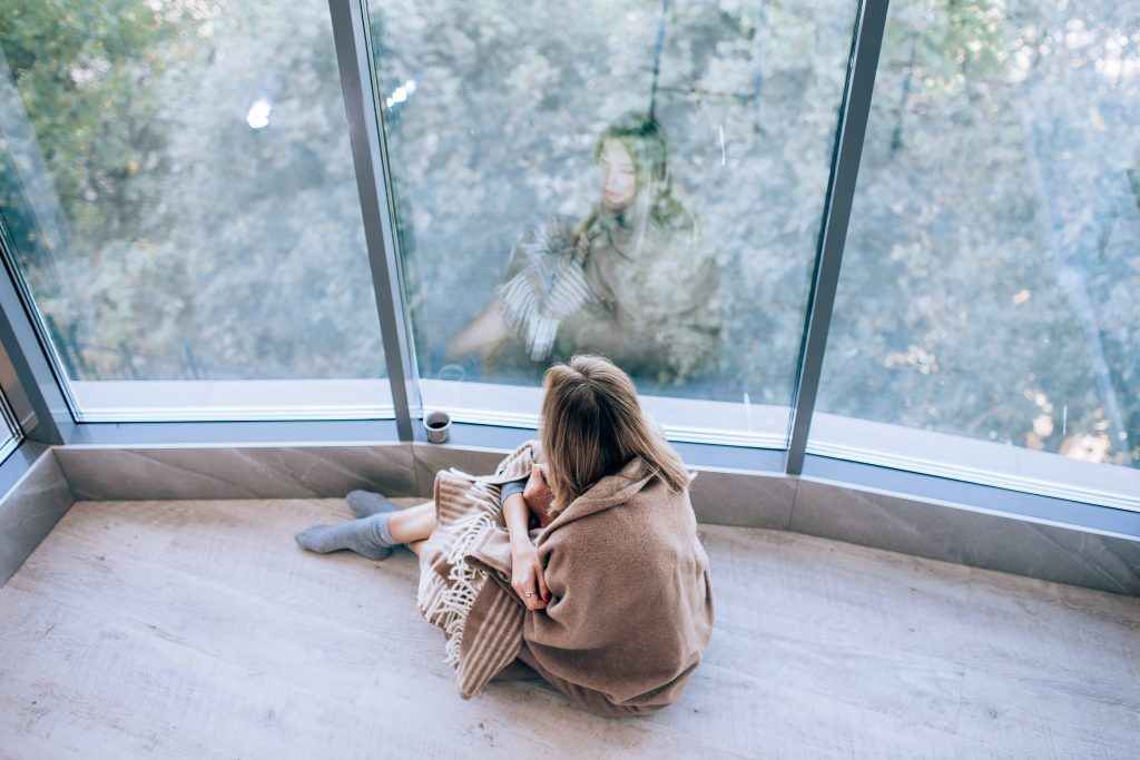 a lonely, sad looking white woman wrapped in a blanket and sitting near a window and looking out thoughtfully