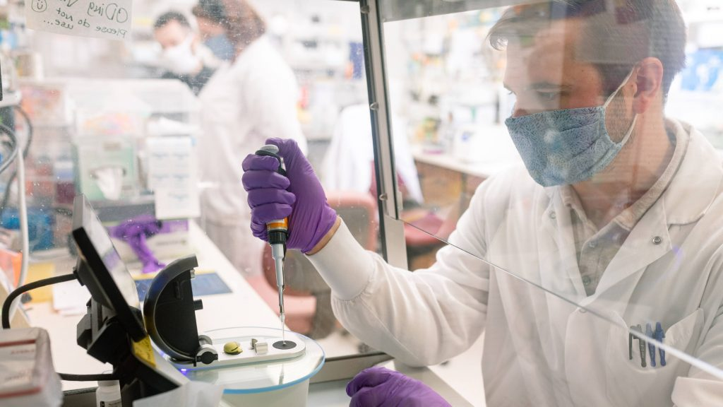 vaccine laboratory researcher earing PPE and working with microscopic samples behind a shield