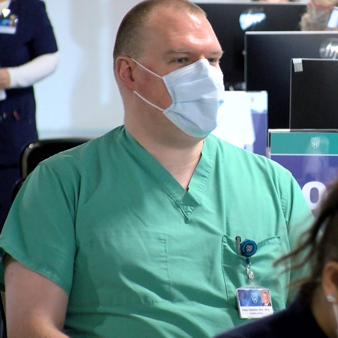 Mayo Clinic's Dr. Casey Clements, a white man, wearing scrubs and a mask while waiting to receive his COVID-19 vaccine