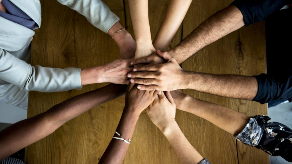 a circle of people's hands and arms coming together as a diverse community like a work team