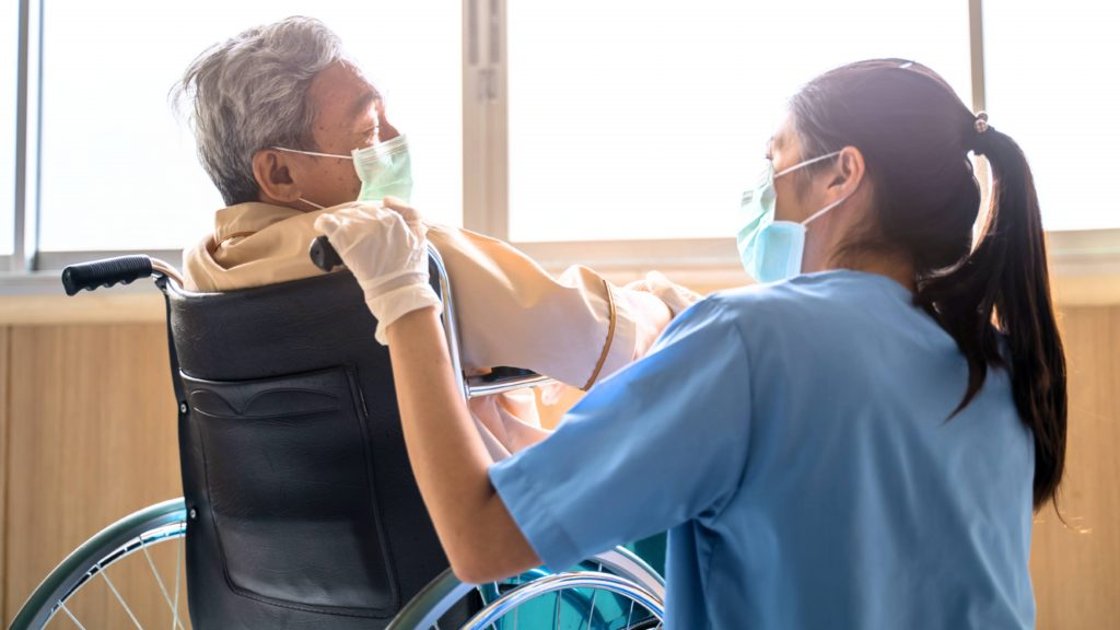 an elderly man, perhaps Asian, wearing a mask and sitting in a wheelchair near a window with a health care worker, a female nurse perhaps Asian or Latina, wearing COVID-19 PPE