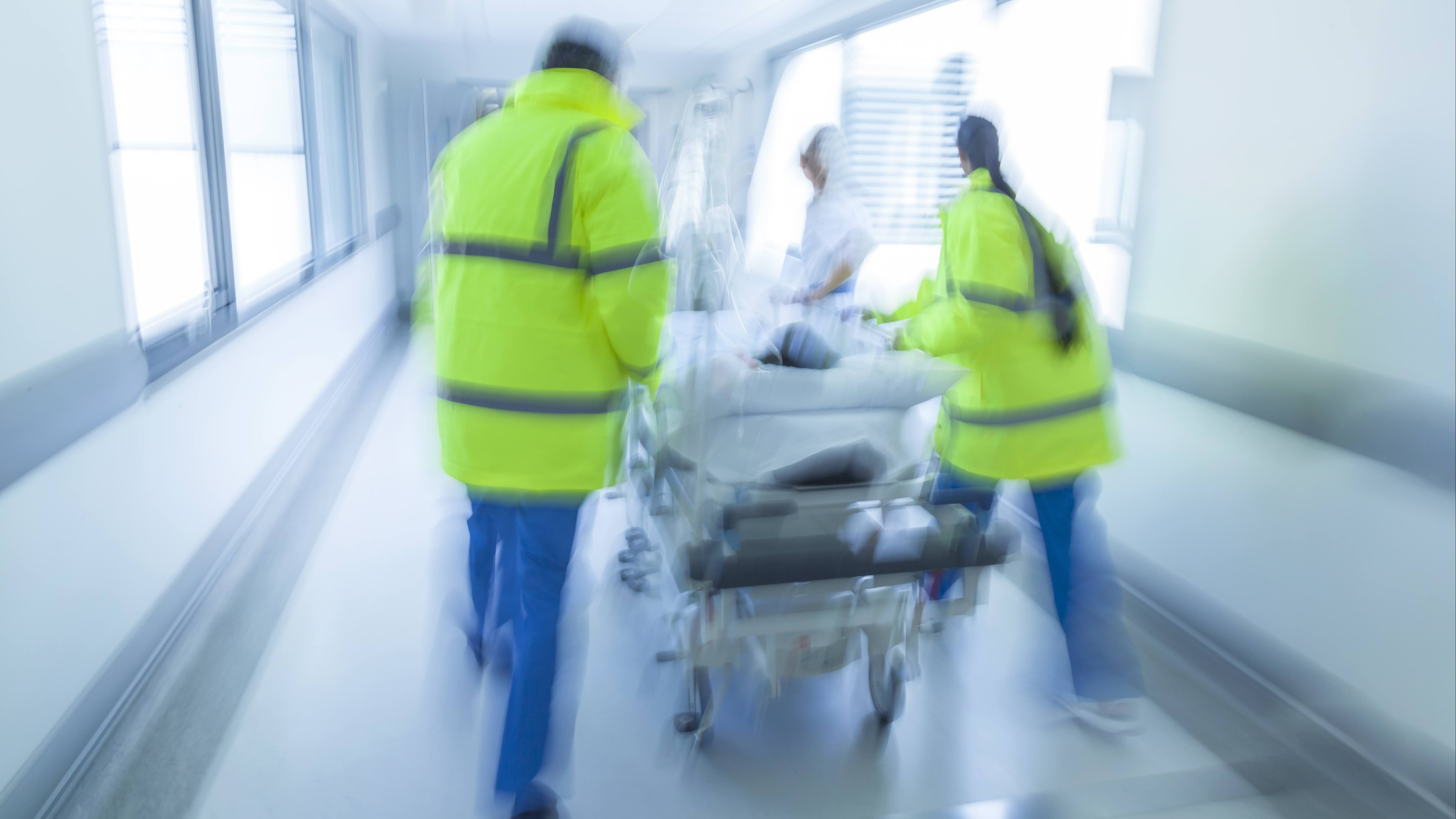 a slightly out of focus image of a hospital hallway with emergency staff walking quickly pushing a gurney with an injured patient