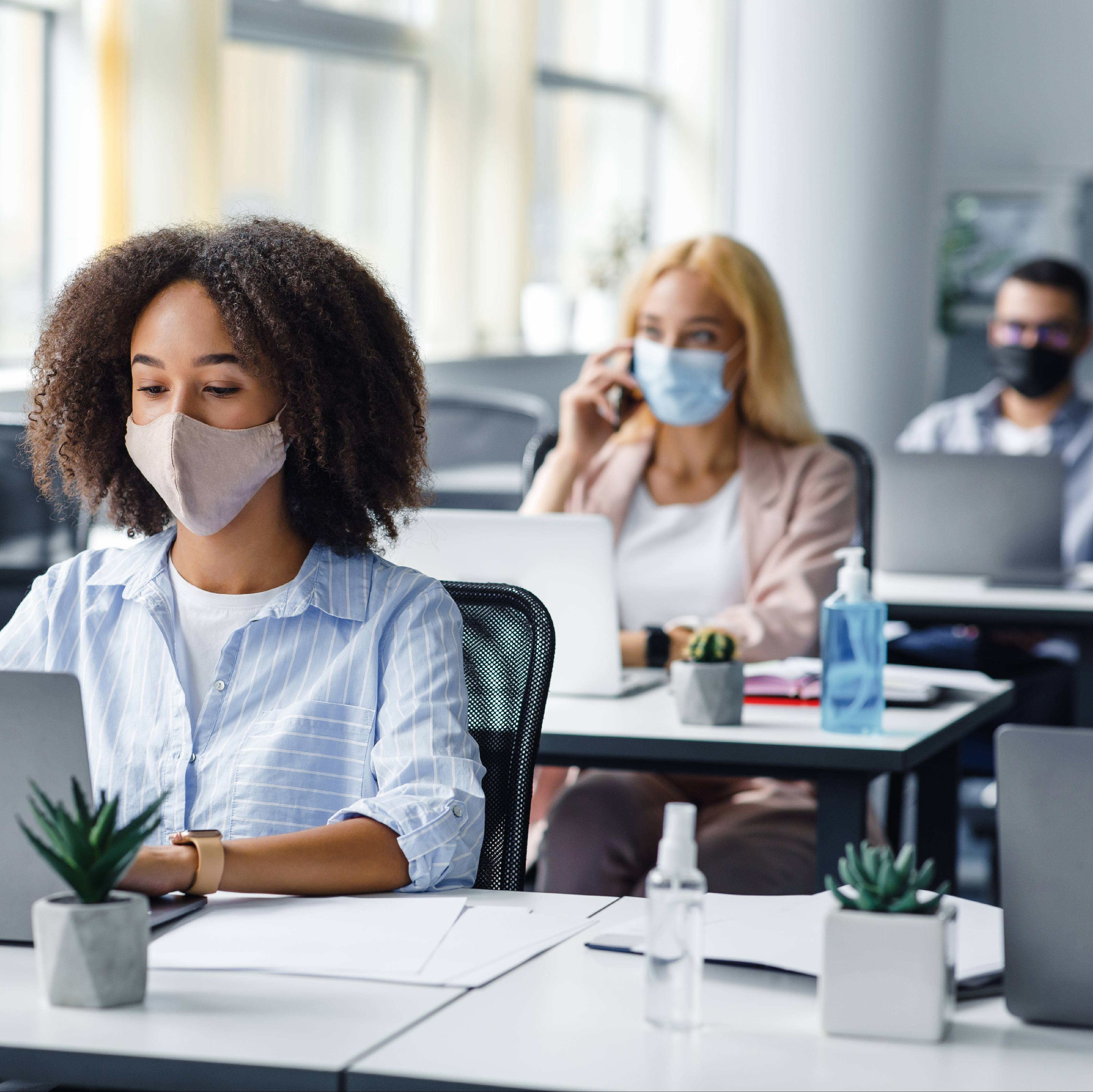 three young diverse students or business people in an office wearing face masks and sitting six feet apart at work desks for COVID-19 social distancing