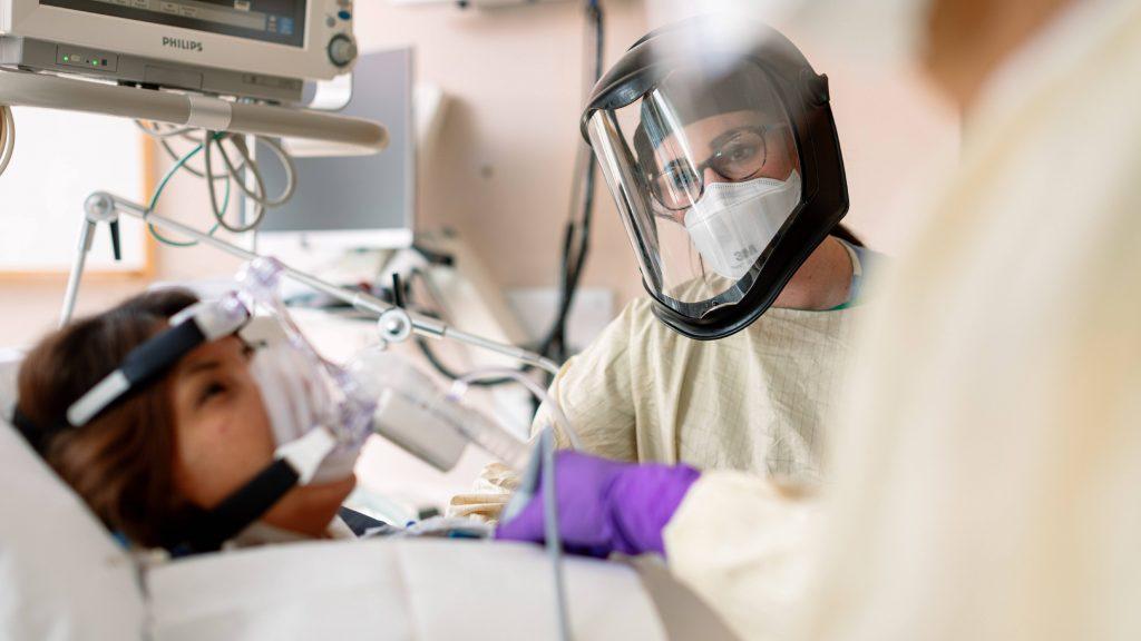 El personal médico de la Unidad de Cuidados Intensivos en Mayo Clinic ataviado con equipo de protección individual ayuda con el respirador a un paciente con COVID-19.