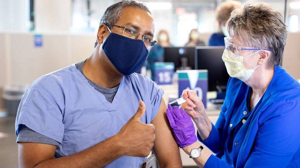 a Black man, Mayo Clinic medical worker in blue scrubs and wearing a mask while receiving a COVID-19 vaccine from a fellow Mayo employee, a white woman wearing PPE