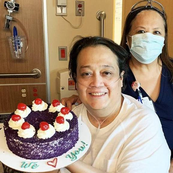 transplant patient, George Caceres, in the hospital wearing an oxygen tube and holding a decorated cake