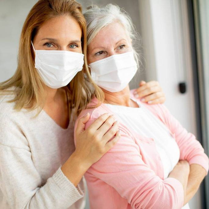 Two white women, perhaps and mother with gray hair and daughter, wearing masks and standing close together near a window