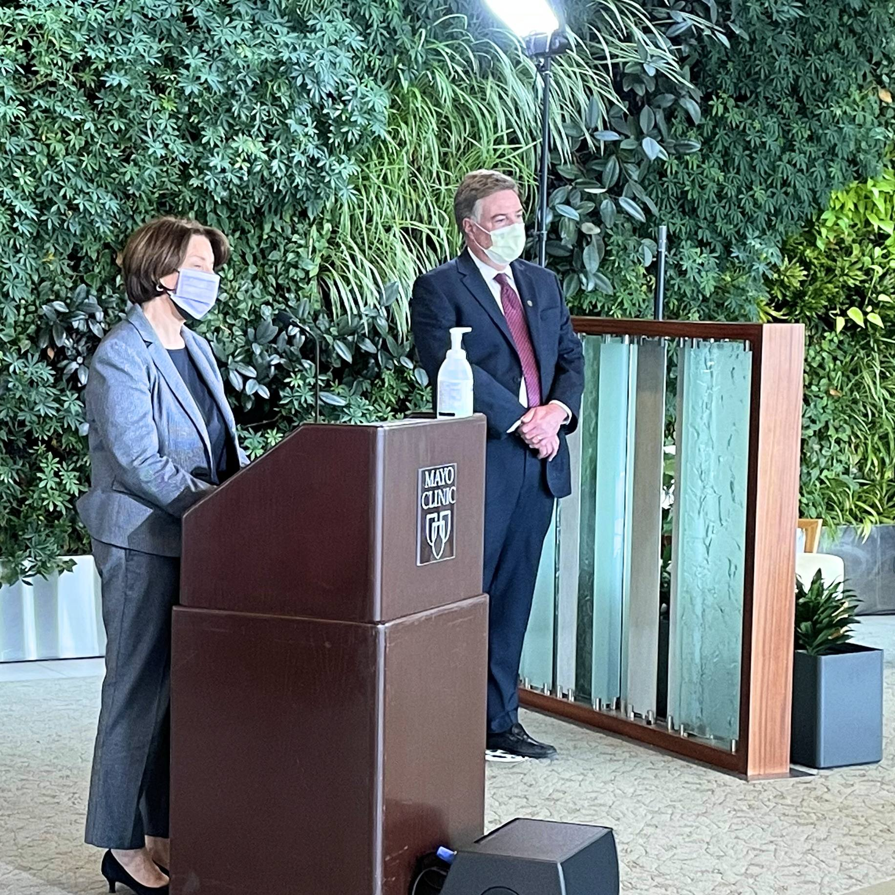 U.S. Senator Amy Klobuchar wearing a mask standing at a podium speaking at news conference with Dr. Andrew Badley, wearing a mask, standing at a distance