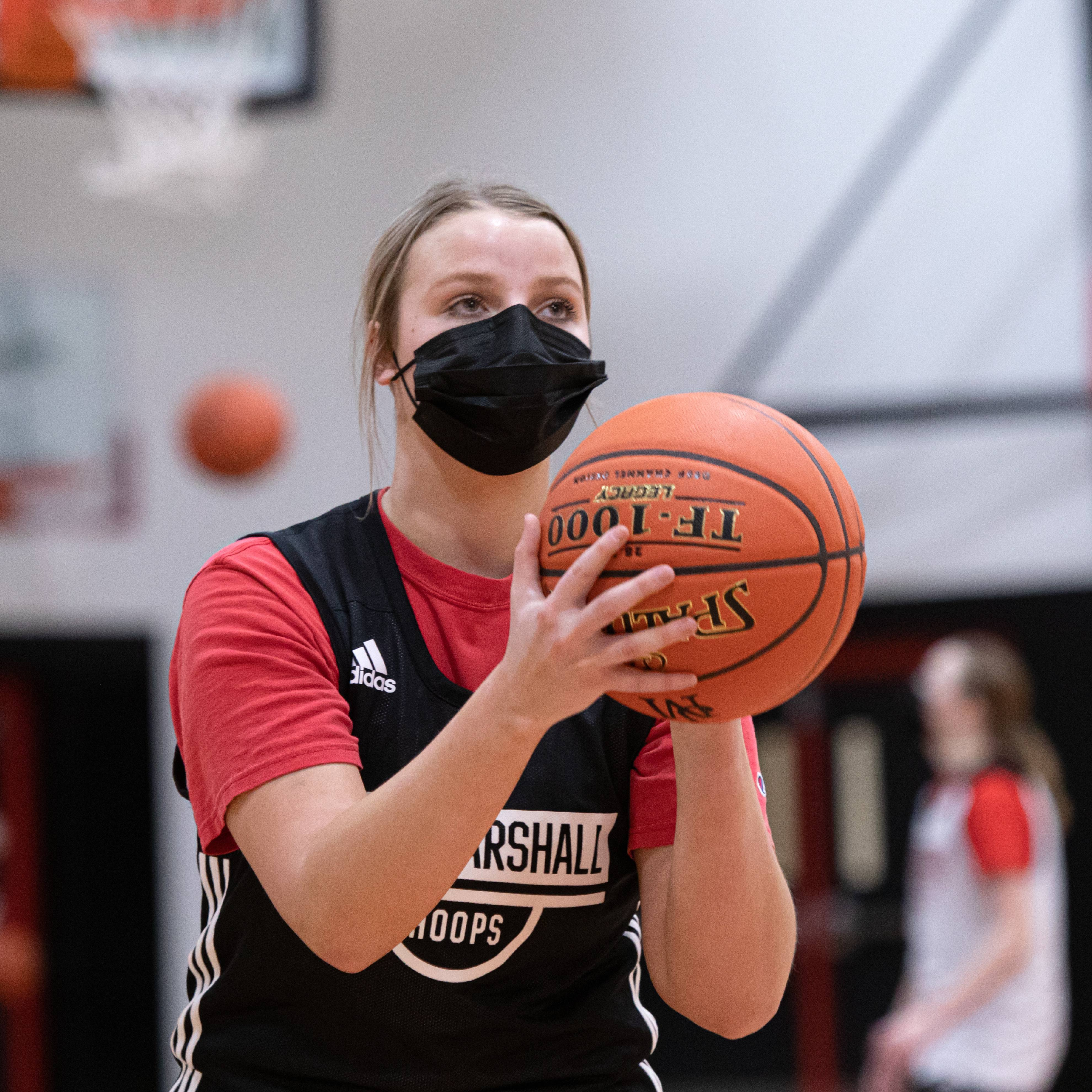 a high school basketball player, a white girl, wearing a uniform and face mask, getting ready to shoot a basketball