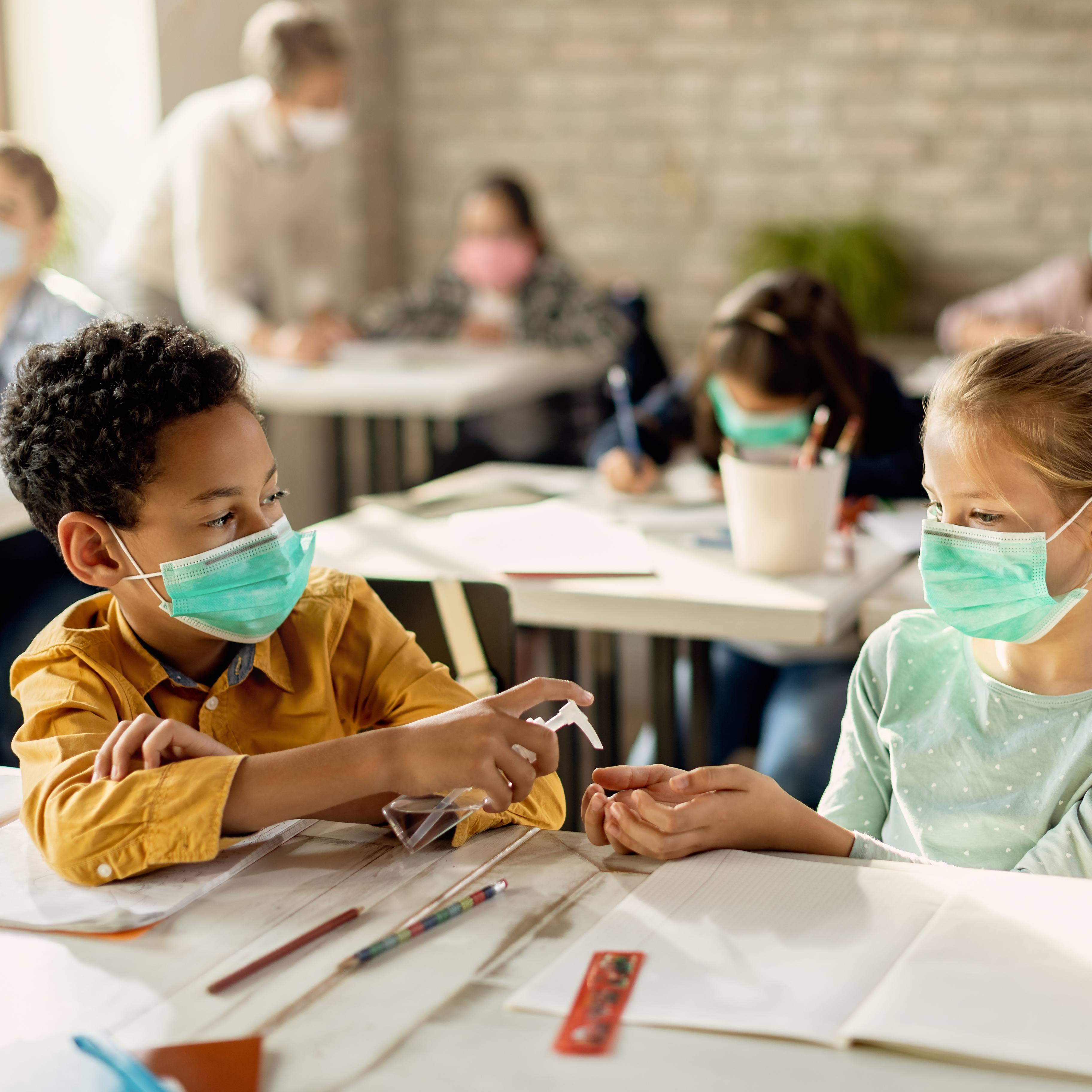 two young children, a Black boy and a white girl, in a school classroom wearing masks, sitting at desks sharing hand sanitizer