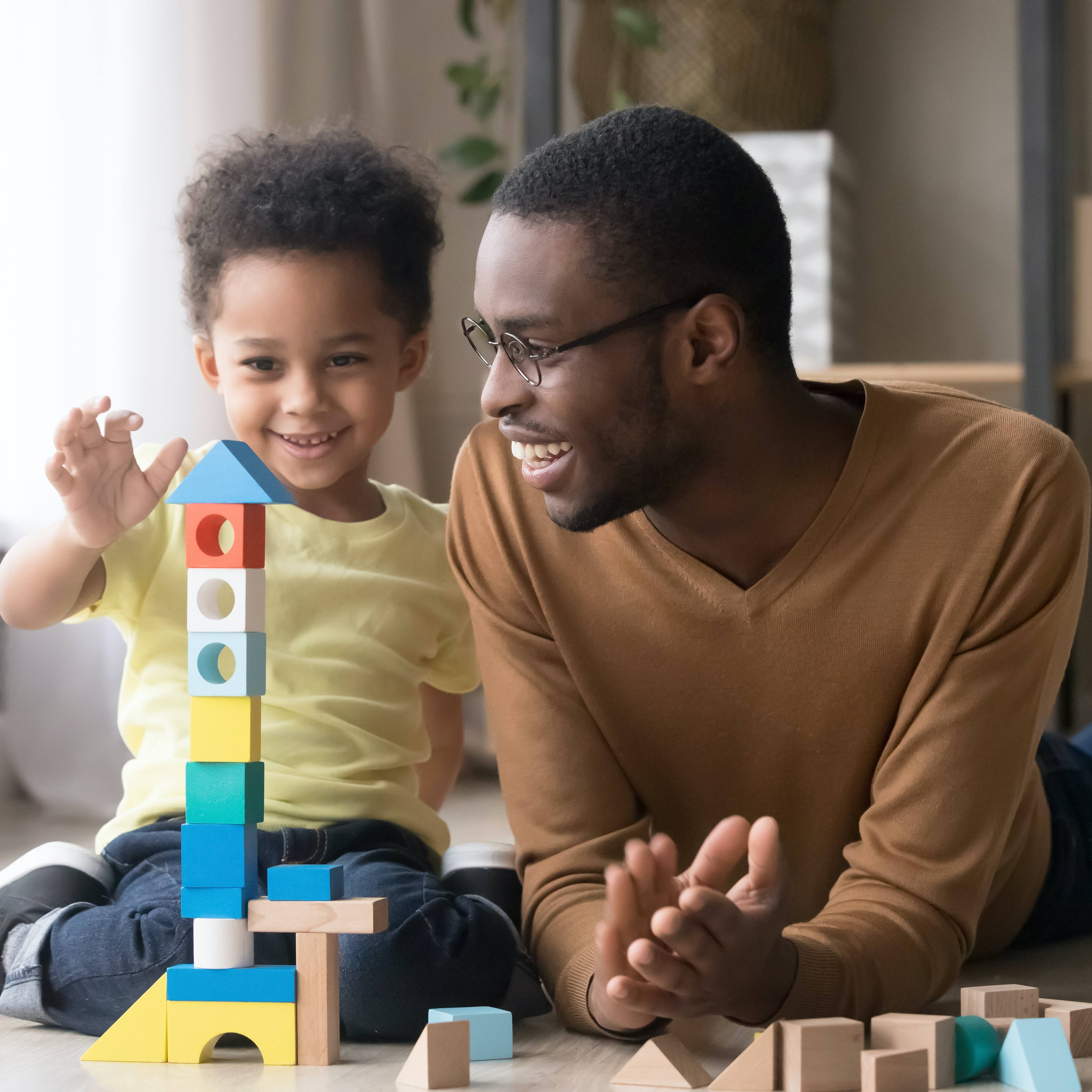 Happy cute little son playing game with black dad building blocks_