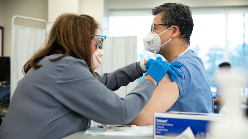 Mayo Clinic medical staff person (a white woman) wearing PPE administering a COVID-19 vaccine to a a man, perhaps Asian American, also wearing PPE