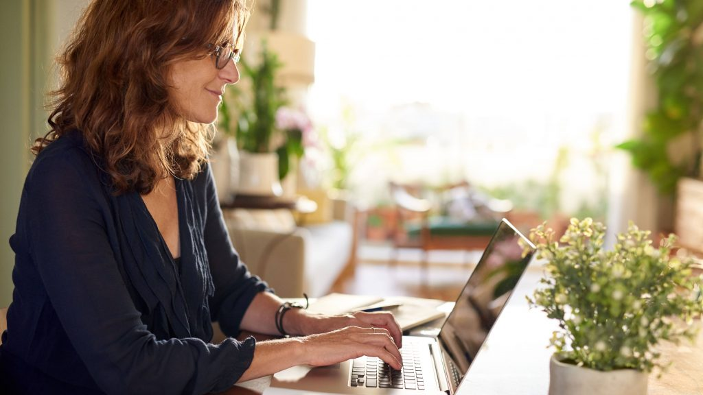 a middle-aged white women with red hair and glasses on a laptop at home or an office, with green plants near a window