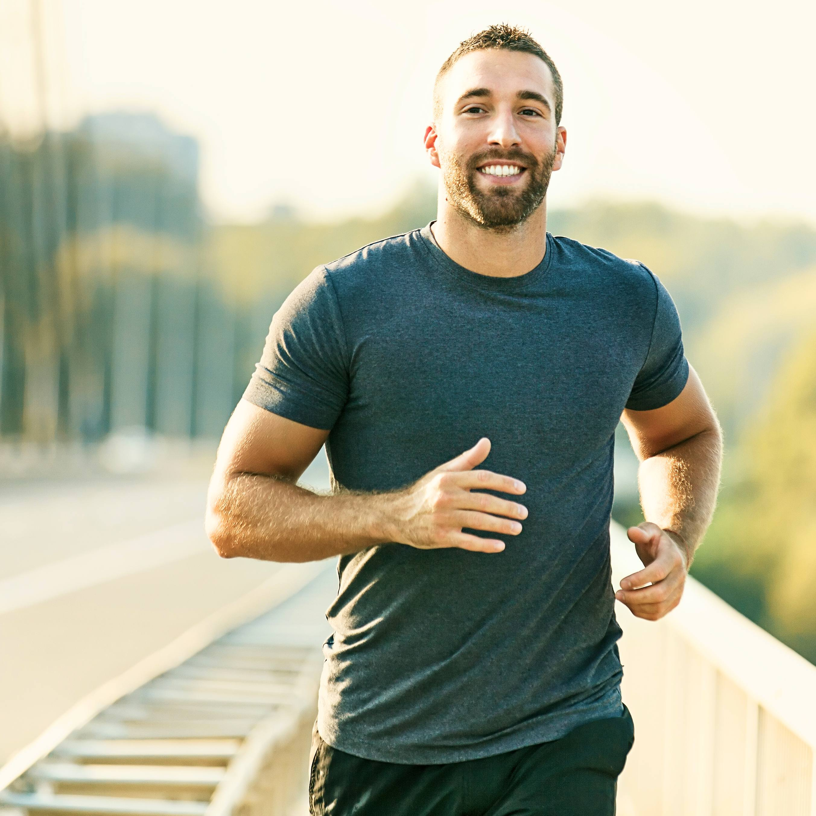 a young white man smiling while running, jogging, exercising outside
